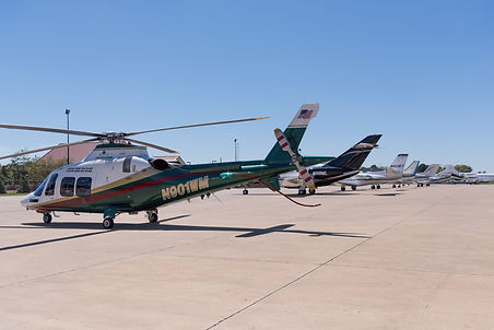 N901WM A109 helicopter parked in Oxford MS along a row of corporate jets