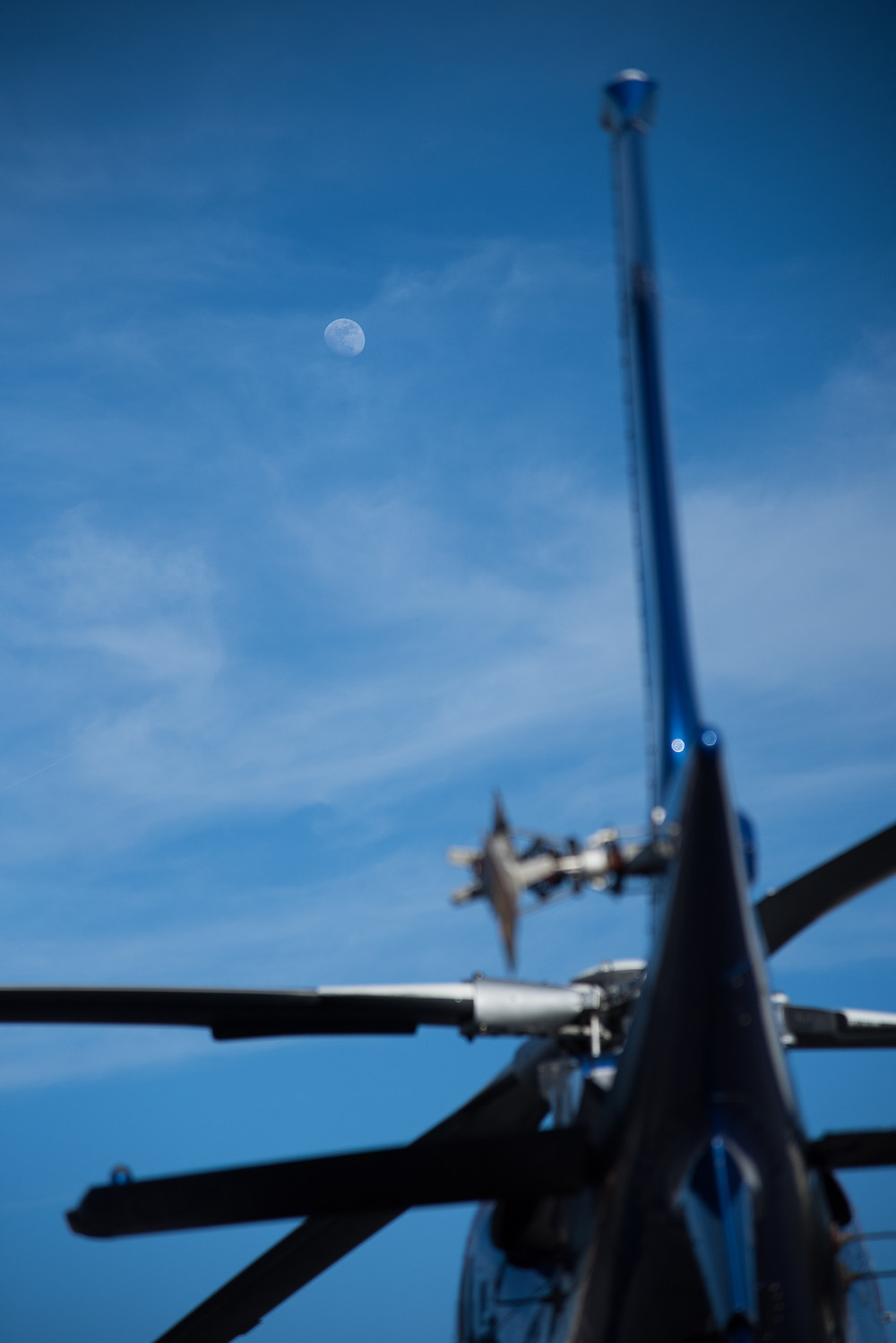 Moon over Augsta Helicopter against bright blue sky in Arkansas