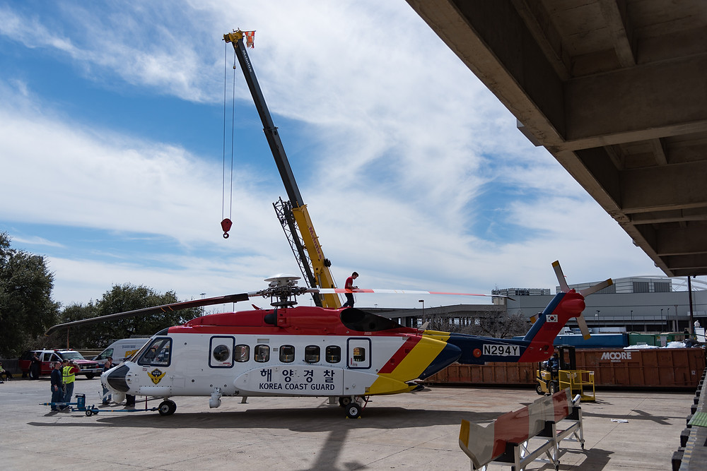Sikorsky S92 helicopter uses a crane to remove the blades for transport into the convention center heli expo 2017