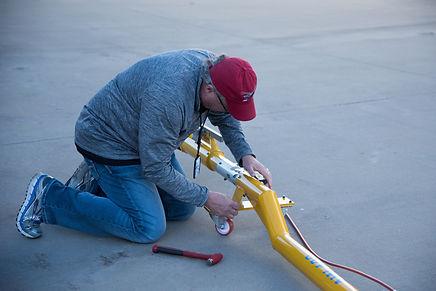 Kenny Mize director of Rotorwing Maintenance assembling the tow bar at the SevenBar hangar