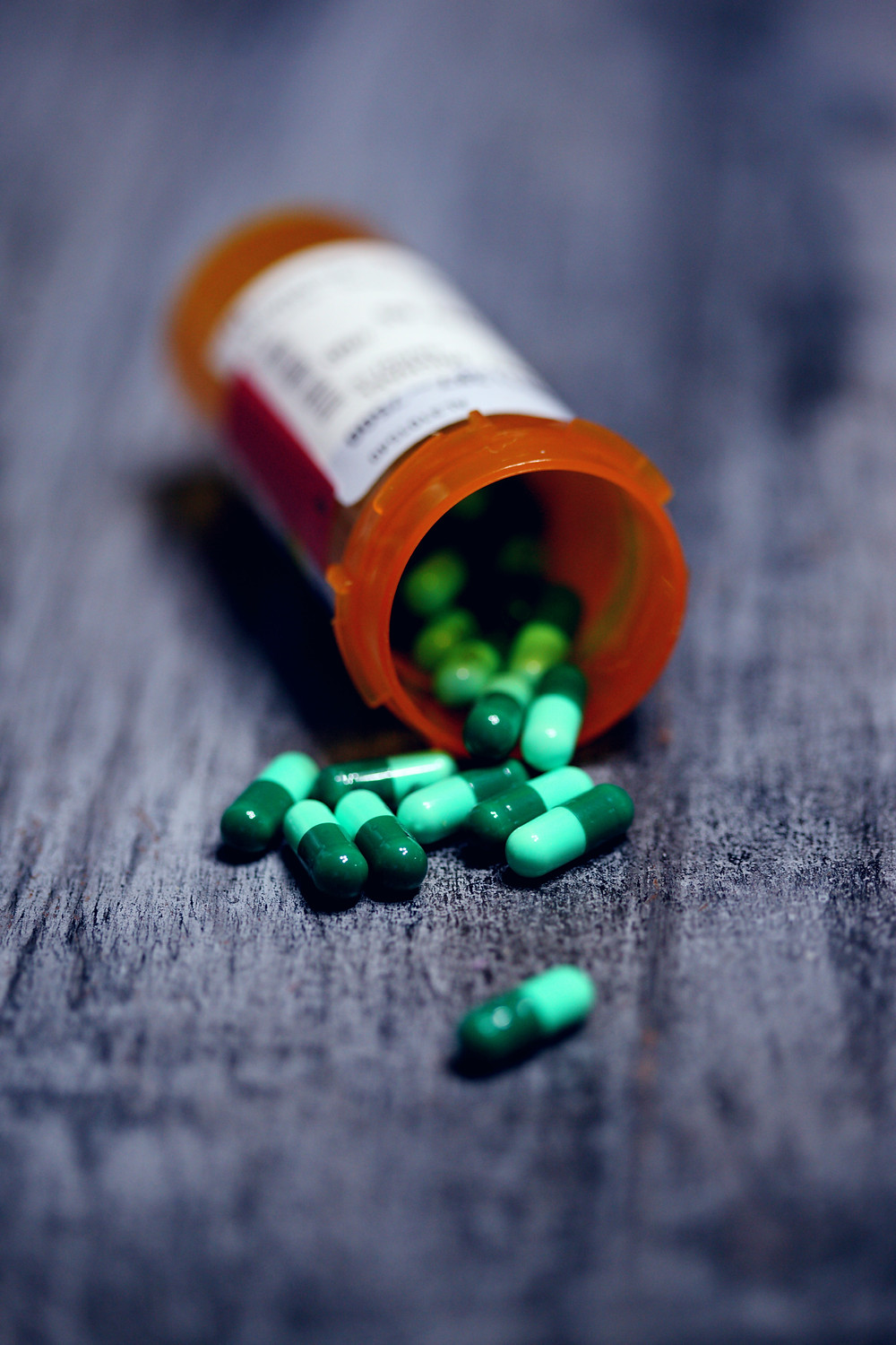 Pill bottle with green capsules spilling out