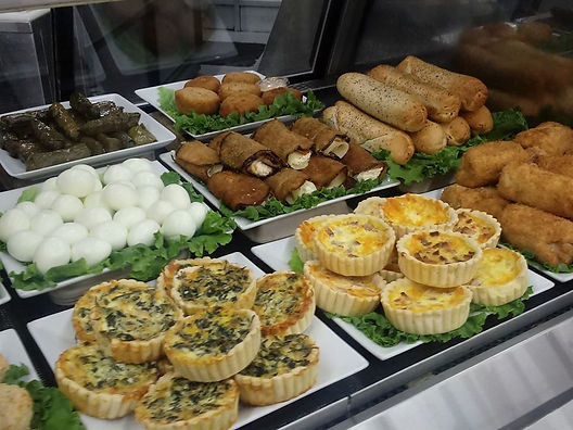 A selection of quiches, bagel dogs, stuffed zucchini, hard boiled eggs & dolmas.