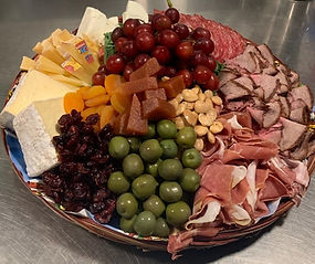 A picture of a cheese & meat tray. Selections of salami, roast beef, various cheeses, fruits & olive