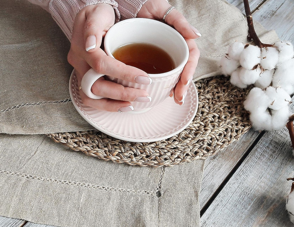 Woman holding tea cup with French manicure and neutral farmhouse decor