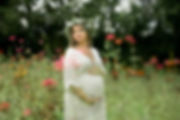 Pregnant mother wearing white maternity gown and floral crown stands in a field of vibrant zinnias waiting, hugging her belly, thinking about her baby