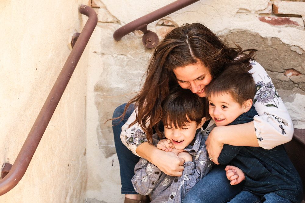 mother hugs two laughing sons during mommy and me motherhood photography session family photography