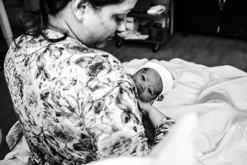 Latina mother breastfeeds her newborn in the hospital after birth documented by motherhood photographer