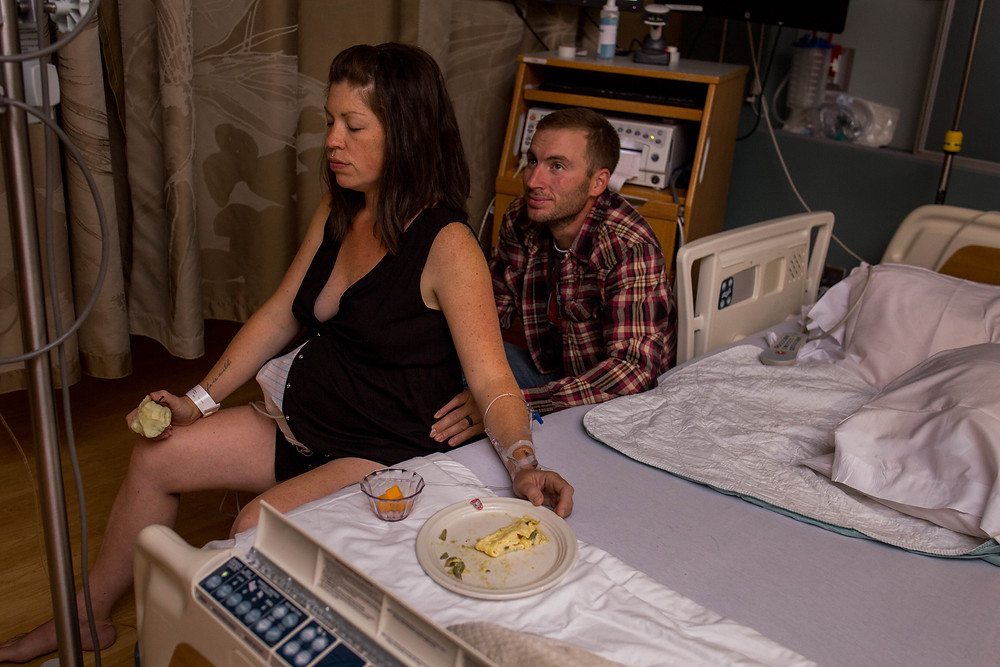 Laboring mother sits on birth ball as she rocks through contractions, taking breaks to eat a nutritious snack during labor while her husband provides hip squeezes