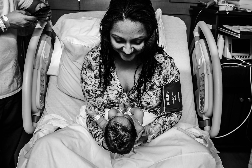 New mother gazes into the eyes of her newborn baby right after being born in a fast labor in South New Jersey