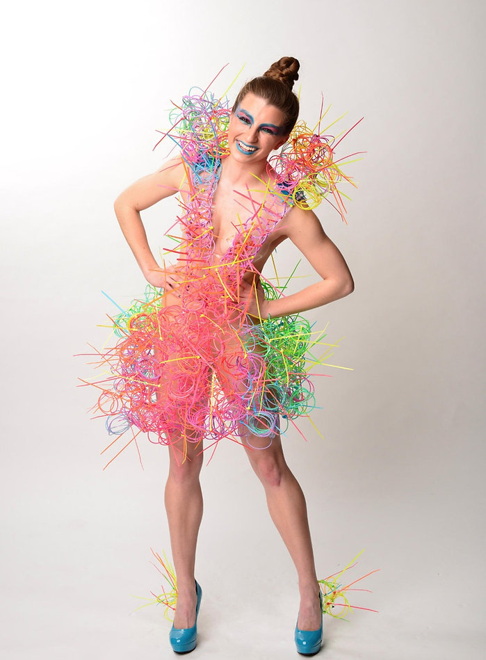 "Multi-colored avant-garde off-the-body garment entitled ""Plunge"" constructed entirely of neon slinky's and zip-ties inspired by the transition into adulthood and the organized and chaotic mess that I've known it to be by Michigan State University Apparel and Textile Design Student Sara Stanzler aka The Golden Haired Girl"