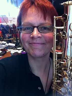 female musical instrument repairer holding a saxophone and smiling. Kate Reynolds Brighton UK