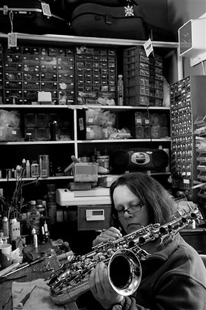 A musical instrument repairer of wind instruments fixing a saxophone. Kate Reynolds - fabkate in her Hove workshop