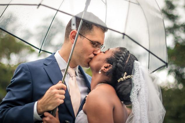 Bride and groom kissing under umbrella.