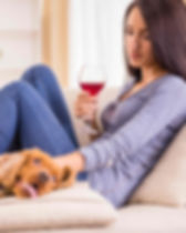 Woman sitting on couch holding red wine with dog