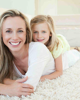 Mother and daughter on clean white carpet or rug