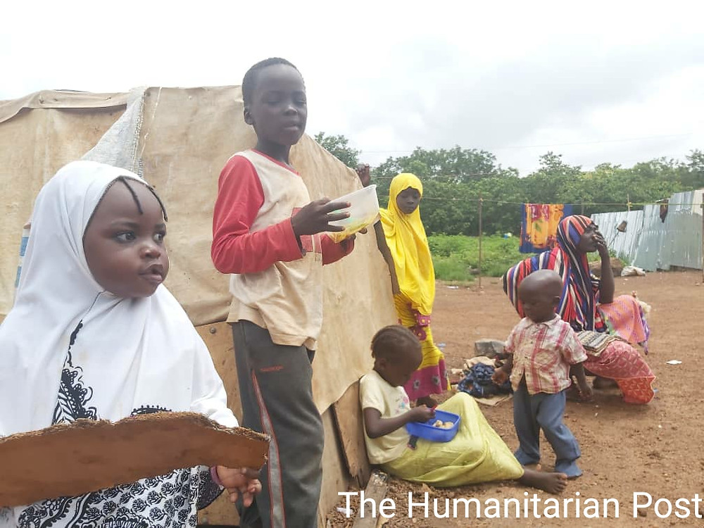 Some Internally Displaced Persons in Durumi sitting around a make-shift hut