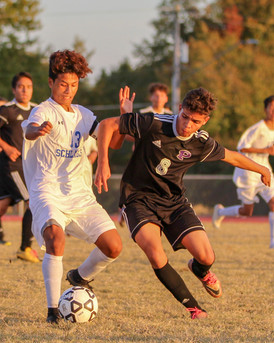 Junior Jorge Narvaez snatches the ball from his opponent from F.L. Schlagle. The Dragon varsity soccer players won the Oct. 23 match against Schlagle 3-2, qualifying them for the second round of the Class 5A Kansas Regional Championship against Saint Thomas Aquinas, which they lost 0-6.