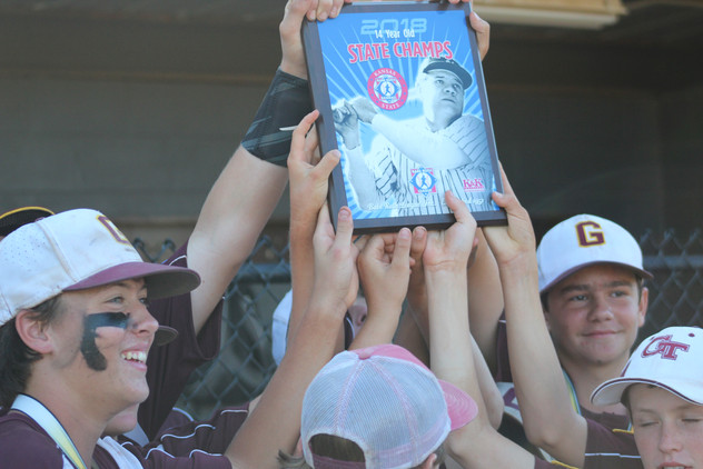 """The Girard 14U All-Stars hold up their Kansas Babe Ruth State Tournament Championship plaque. The Trojans' 11-8 victory against the Liberal Rattlers allowed them to capture this crown. """"I'll remember [the moment] we won,"""" said Gage Davenport, one of Girard's All-Stars, who scored to tie with the Rattlers at 6-6. """"It's kind of like being in the World Series."""""""