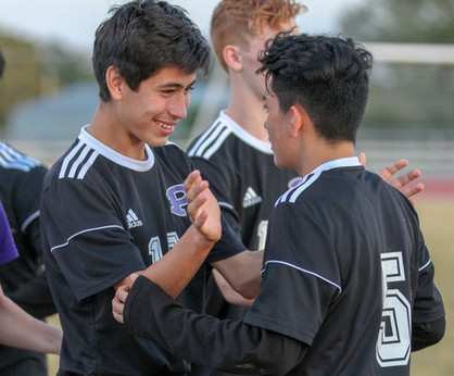 Freshman soccer player Shane Baeza pats freshman player Bryan Rueda on the back after their 3-2 victory against F.L. Schlagle. This win qualified the Dragon varsity soccer players for the second round of the regional championship against Saint Thomas Aquinas, which they lost 0-6.