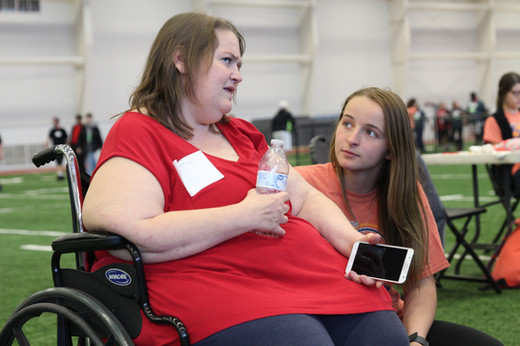 """Junior Morgan Noe, a member of the Get Busy Livin' (GBL) Club, converses with a Special Olympics athlete before awards. Noe, as well as 18 other members of the club, volunteered at the Special Olympics Track and Field tournament on Thursday, April 18 at the Robert Plaster Center's indoor football field. """"I've gotten more experiences with the club,"""" Noe said. """"I've gotten to help the community and give back, which is what GBL is all about."""""""