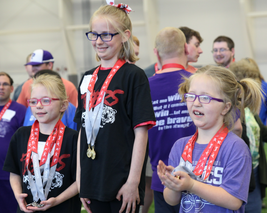 Three elementary school Special Olympic athletes stand on the podium to receive their awards. Photo by Nicole-Marie Konopelko.