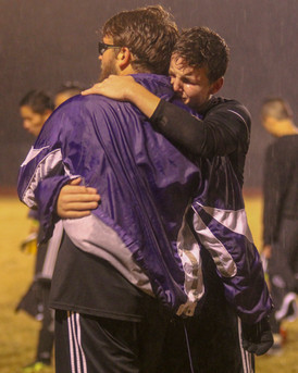 """With tears rolling down his eyes, junior Caden Bressler embraces his senior teammate, Brent McDowell, seconds after their 0-6 loss to Saint Thomas Aquinas on Oct. 25. This loss knocked the Dragon varsity soccer players out of the Class 5A Kansas Regional Championship, and concluded their 2018 season. """"[The loss] was crushing,"""" McDowell said. """"Knowing that was my last game with those guys was rough. It was an amazing season and I wish it could never have ended."""""""