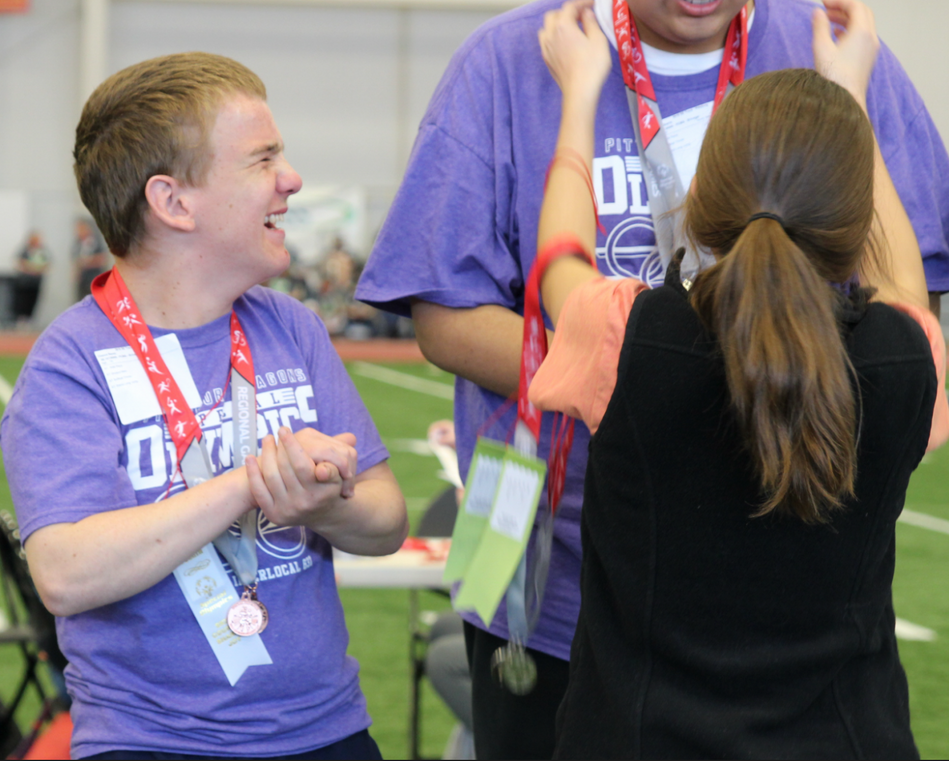 A Special Olympic athlete claps for his fellow classmate as he receives his first place medal. Photo by Nicole-Marie Konopelko.