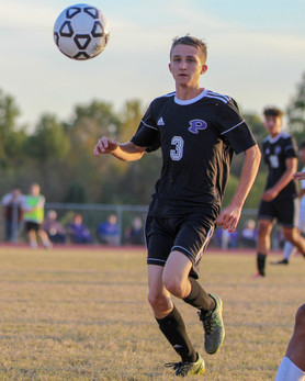 Sophomore Blaker Foster eyes the ball, preparing to kick it. Foster scored two out of the Dragons' three goals against the F.L. Schlagle Stallions, who scored two, during their matchup on Oct. 23.