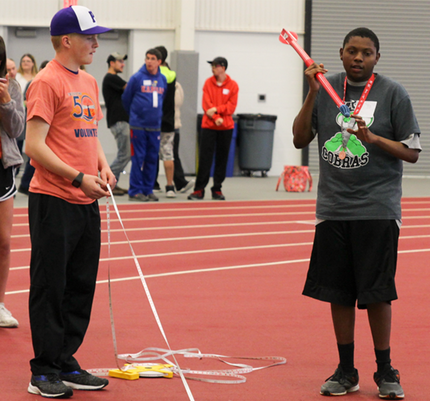 Freshman Cole Jameson, a GBL Club volunteer at Thursday's Special Olympics, hoists the measuring tape as a Special Olympic athlete prepares to throw his javelin. The measurements were used to determine placings for the javelin throw. The Special Olympics is one of the many community service events GBL members have participated in. Photo by Nicole-Marie Konopelko.