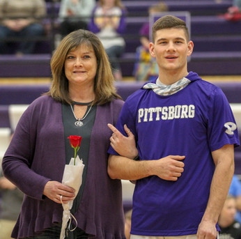 """Senior junior varsity basketball player Ty Roark stands in front of the audience of the Dragons' basketball game against Field Kinley on Thursday, Feb. 21, during halftime, as his mom, Debbie Roark, holds a rose that the cheerleaders gave Ty. This yearly tradition, also known as """"Senior Night,"""" is organized by activities director Jeff Staley to recognize seniors involved in extracurriculars including forensics, cheer, dance and basketball. The seniors walk across the court with their parents and are handed a rose as their names are announced over the intercom."""
