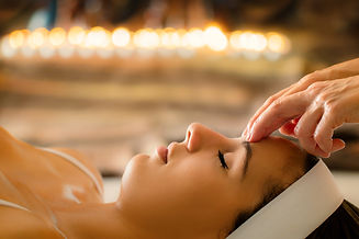 Close up portrait of woman having head massage in spa. Low key atmosphere with out of focu
