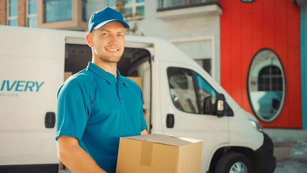 Handsome Courier Takes Cardboard Box Package out of Delivery Van Walks Through Modern Styl