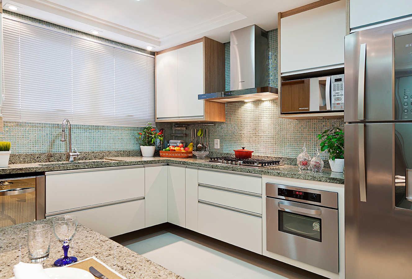 Nesta cozinha  de um casal aposentado, fizemos a  integração do quarto de serviço, abrindo espaço para uma despensa com portas de correr e uma pequena copa para refeições rápidas.