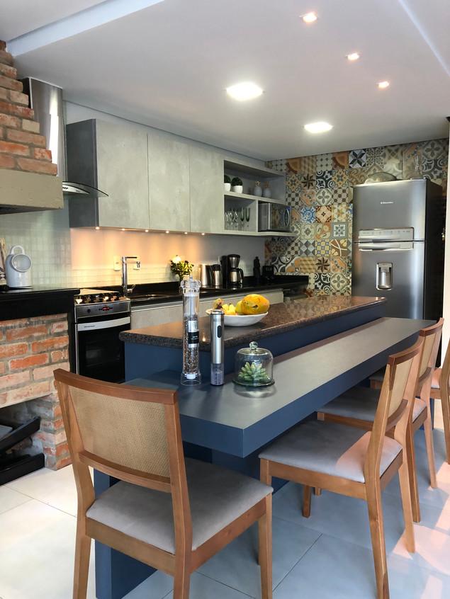 Cozinha  com churrasqueira integrada ao estar, com  balcão tipo ilha na cor azul,  é um ótimo espaço de apoio, acomodando armários e bancada de refeições.