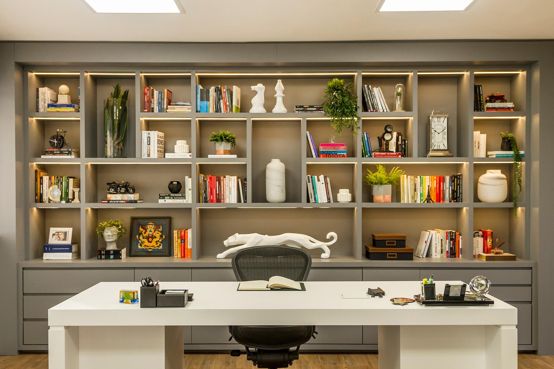 A estante para livros, com iluminação indireta ,traz sofisticação e aconchego  para a sala dos diretores.