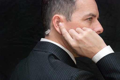 Close-up of a secret service agent listening to his earpiece, side.jpg