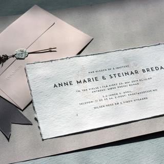 Ren typografi med en krans liggende som et vannmerke i det håndlagde papiret gir et sobert inntrykk.