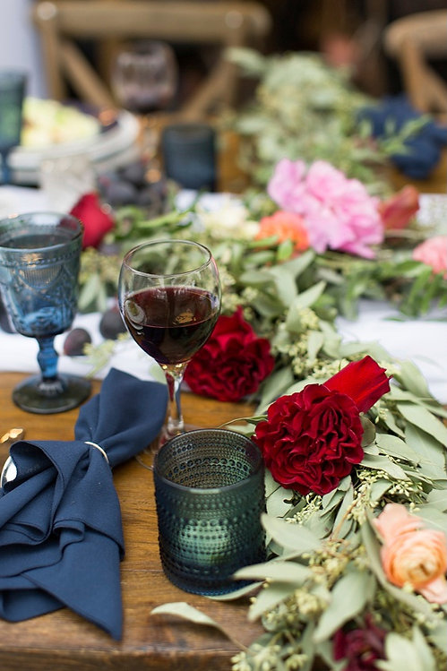 a glass of rwine sits on a wooden table with place settings and floral arrangements