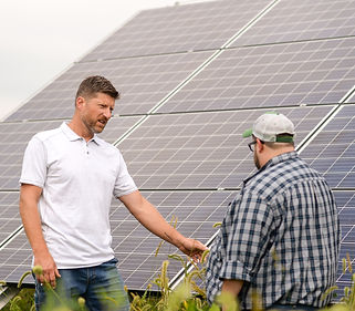 Chris talking to farmer. solar panels in