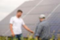 Chris talking to farmer. solar panels in
