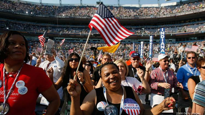 Woman with American flag and large 'Vote Democratic' button standing in crowd at the 2008 Democratic National Convention