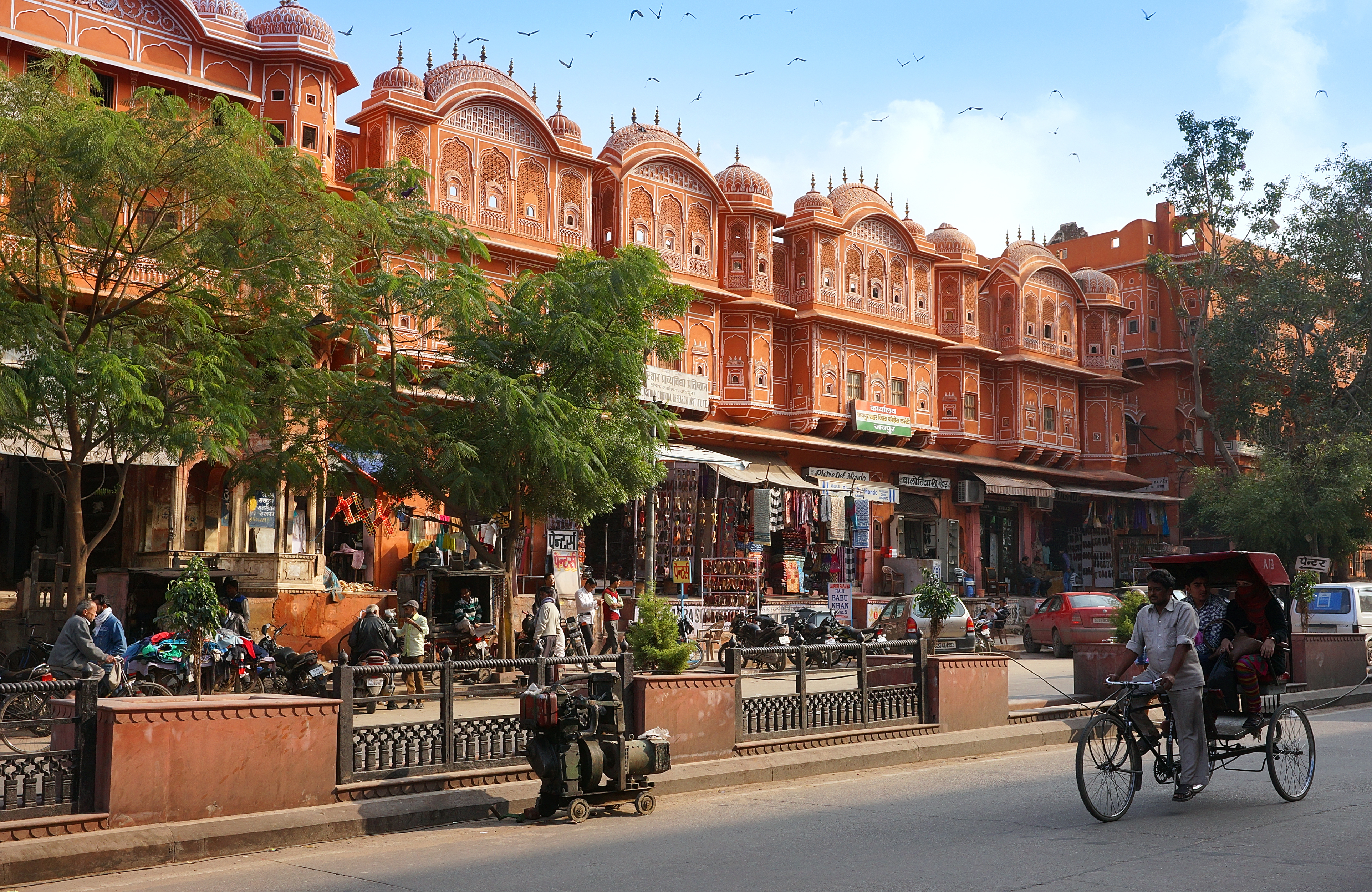 Jaipur, India - January 23,2014  Rickshaw riding his tricycle on the street in front of Hawa Mahal,