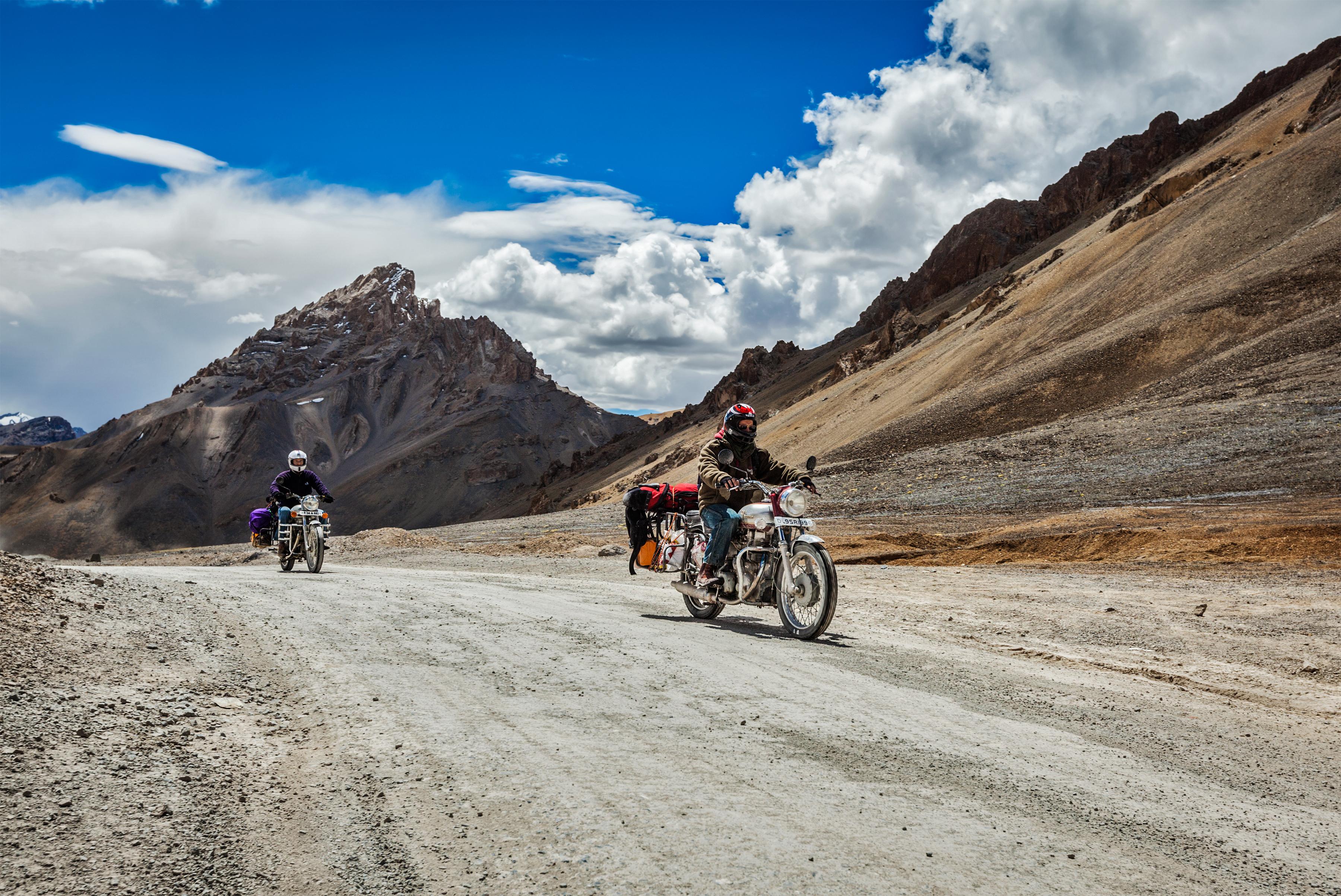 Bike tourists in Himalayas on famous high altitude Leh-Manali Highway. Himalayan bike tourism is gai