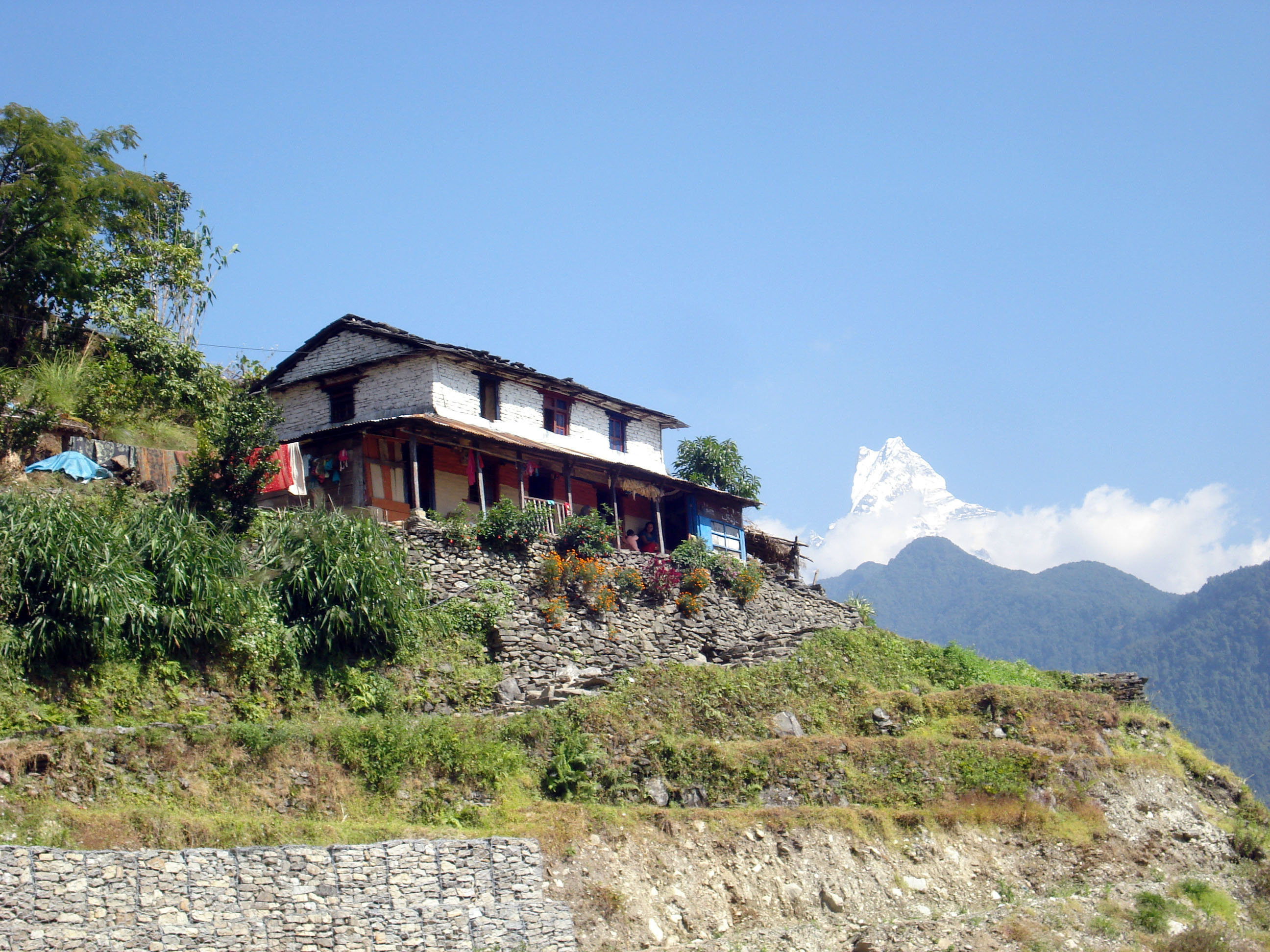 Typical_rural_Nepali_house_with_Mt._Fistail_in_backfround