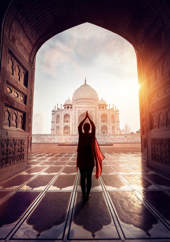 Woman doing yoga tadasana tree pose with flying red scarf in silhouette near Taj Mahal in Agra, Utta