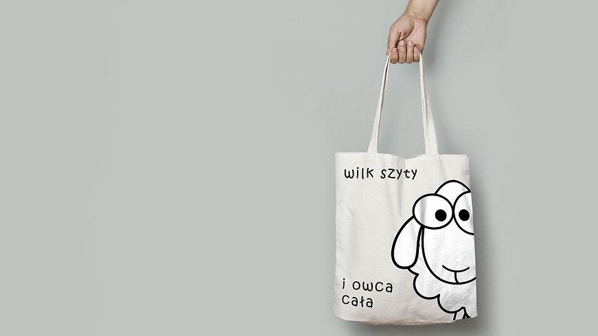 tło przedstawia torbę bawełnianą z napisem wilk szyty i owca cała