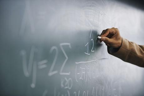 Professor que escreve uma fórmula em um quadro-negro