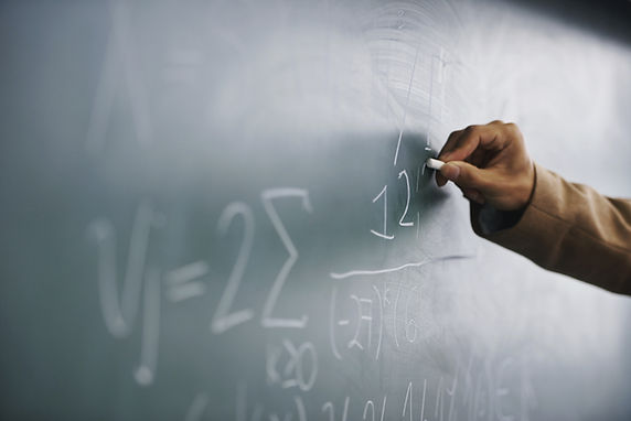 Teacher Writing a Formula on a Blackboar