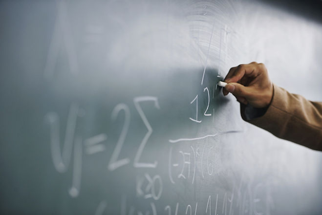 Teacher Writing a Formula on a Blackboard