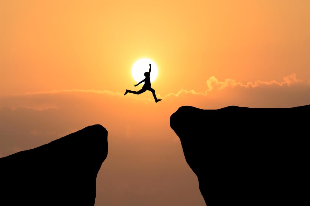 person joyously leaping across a precipice